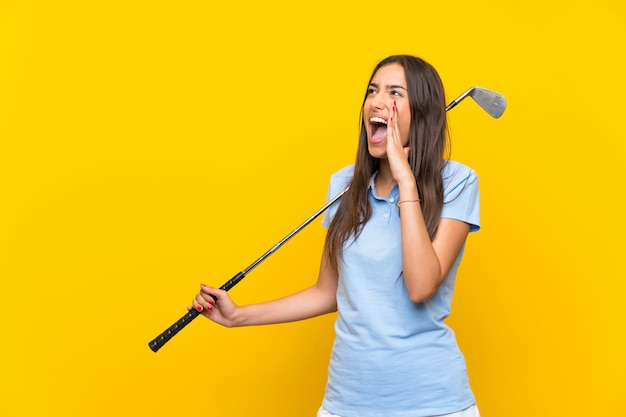 Young golfer woman  isolated on yellow wall shouting with mouth wide open