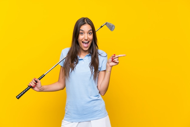 Young golfer woman  isolated on yellow wall surprised and pointing finger to the side