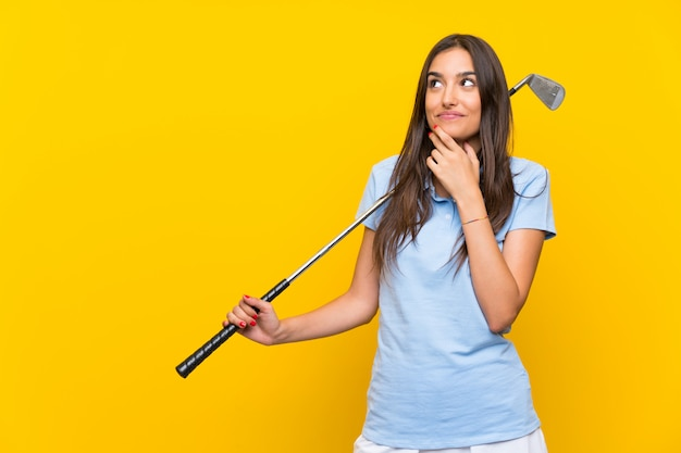 Young golfer woman over isolated yellow wall thinking an idea