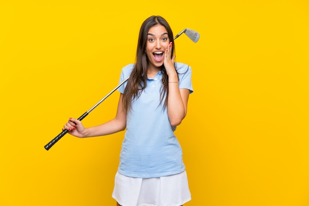 Young golfer woman over isolated yellow wall with surprise and shocked facial expression