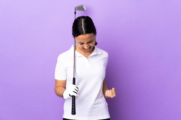 勝利を祝う孤立したカラフルな上の若いゴルファーの女性
