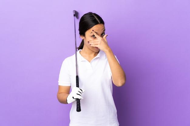 手と笑顔で目を覆う孤立したカラフルな上の若いゴルファー女性