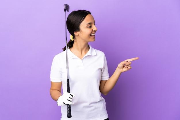 指を持ち上げながら解決策を実現しようとしている孤立したカラフルな壁の上の若いゴルファーの女性