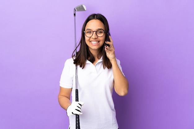 누군가와 휴대 전화로 대화를 유지하는 고립 된 다채로운 벽 위에 젊은 골퍼 여자