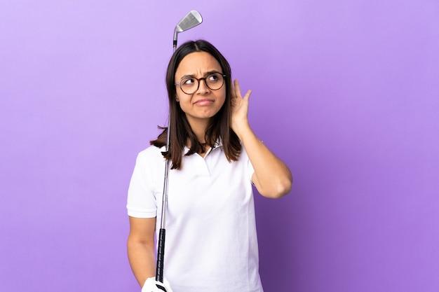 耳に手を置くことによって何かを聞いている孤立したカラフルな壁の上の若いゴルファーの女性