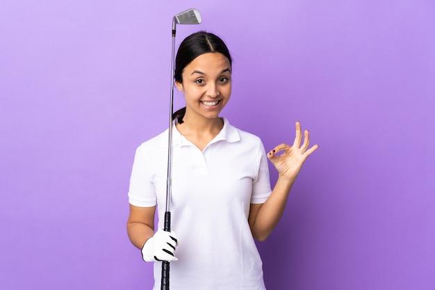 손가락으로 확인 표시를 보여주는 고립 된 다채로운 벽 위에 젊은 골퍼 여자