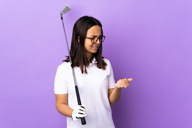 Молодая женщина-гольфист над изолированной красочной стеной, страдающей от боли в руках