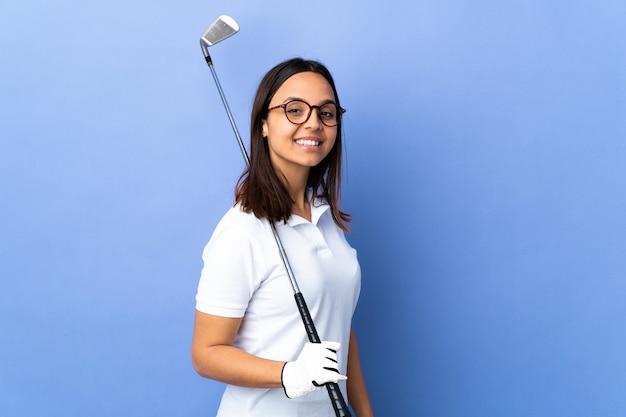 腕を組んで、楽しみにして孤立したカラフルな壁の上の若いゴルファーの女性