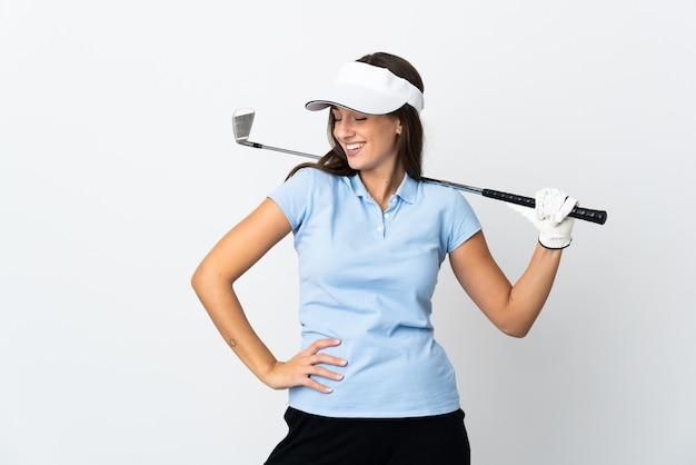 腰に腕と笑顔でポーズをとって孤立した白い壁の上の若いゴルファーの女性