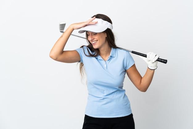たくさん笑って孤立した白い壁の上の若いゴルファーの女性