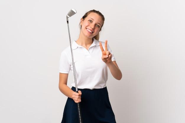 웃 고 승리 기호를 보여주는 격리 된 흰 벽 위에 젊은 골퍼 여자