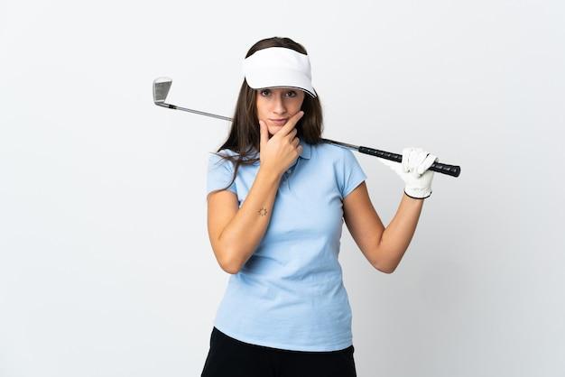 孤立した白い壁の思考の上の若いゴルファーの女性