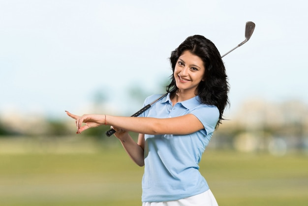 Young golfer woman pointing to the side to present a product at outdoors