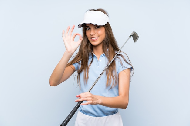 Young golfer woman showing ok sign with fingers