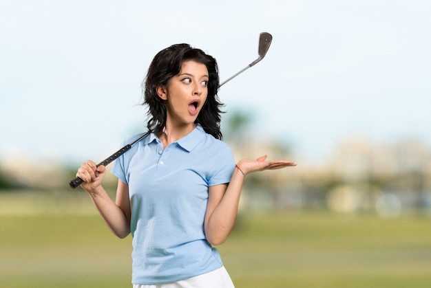 Young golfer woman with surprise facial expression at outdoors