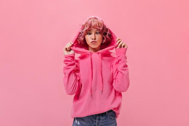 분홍색 까마귀를 입은 유머러스한 젊은 여성이 웃긴 얼굴을 만든다