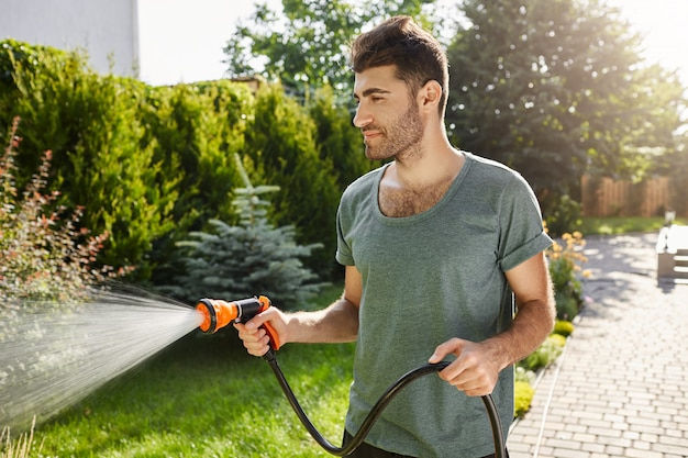 Young good-looking bearded caucasian man with stylish hairstyle in blue t-shirt concentrated watering garden with hose.