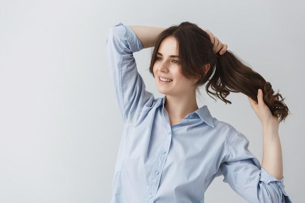 Молодая красивая кавказская девушка делает прическу, готовясь к выходу рано утром с счастливым выражением лица.