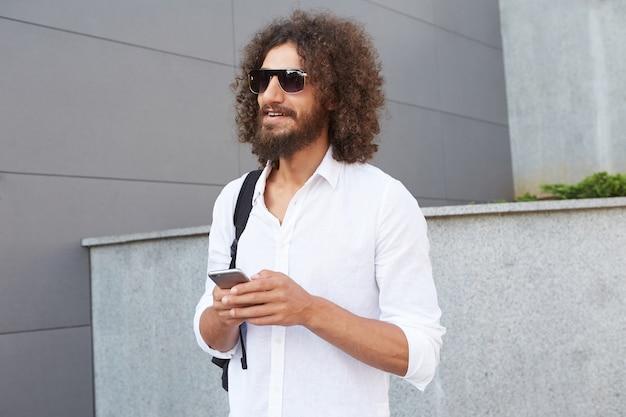 Bello giovane uomo riccio con la barba che tiene smartphone e sorridente, indossando abiti casual e occhiali da sole