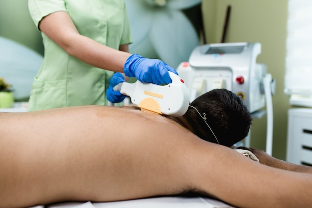 Young good looking man getting hair removal cosmetology procedure at cosmetic beauty spa clinic.