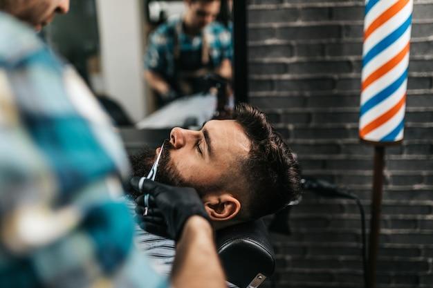 理髪店を訪れる若い格好良い男。トレンディでスタイリッシュなあごひげのスタイリングとカット。