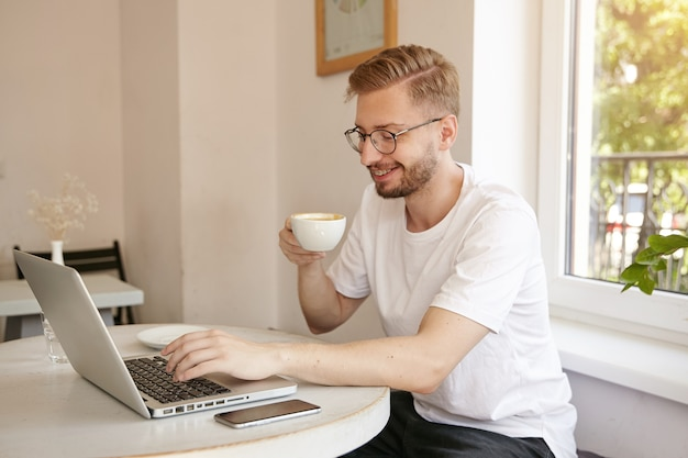 Young good looking man with beard is sitting at table in cafe and drinking coffee while typing text on his laptop, smiling and being in nice mood