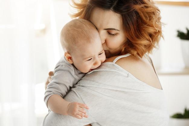 若い格好良い母親が泣いている赤ん坊を抱擁し、落ち着かせます。子供が叫び、母の肩で泣いています。保護と愛のシーン。家族の概念。