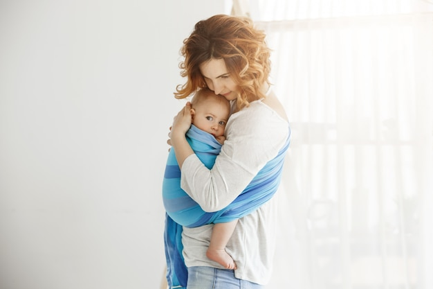 若いハンサムな母親が寄り添い、通りからの大きな音に邪魔されて長い睡眠の後に恐怖を感じている彼女の生まれたばかりの息子を落ち着かせます。保護と愛のシーン。