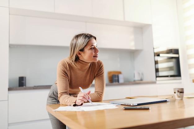 台所のテーブルに寄りかかって、自宅の台所に立っている間、請求書を埋める若いゴージャスな金髪の実業家。