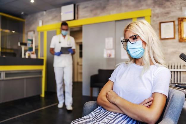 Молодая великолепная белокурая женщина с маской для лица сидит в больнице со скрещенными руками и ждет вызова врача.