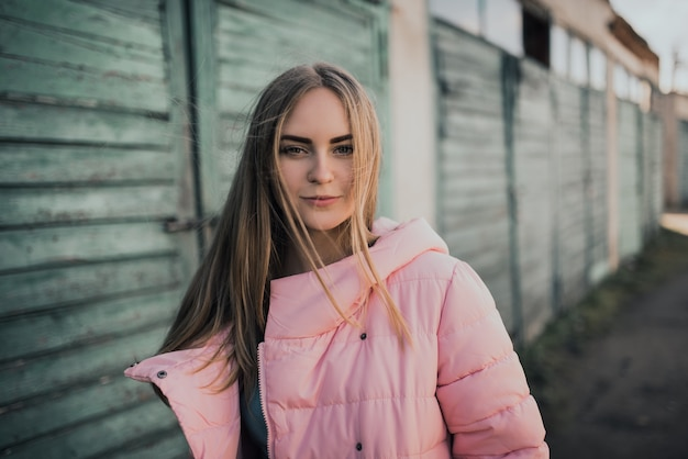 若いゴージャスなブロンドの女の子は、ファッションのピンクのジャケットとブルージーンズを着ています。