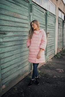 Молодая великолепная блондинка одета модный розовый пиджак и синие джинсы.