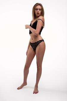 Молодая великолепная блондинка в черном кружевном нижнем белье