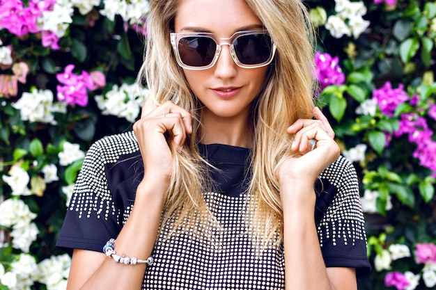 Young gorgeous blonde young woman , wearing stylish outfit, trendy sparkled crop top and sunglasses, posing in floral garden