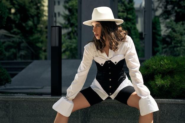 Молодая великолепная бизнес-леди позирует, офисное здание на городской улице. стильная женская модель в белой рубашке, сексуальном черном корсетном поясе и шляпе, глядя в сторону. понятие моды.