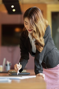 Young gorgeous businesswoman lean on office desk and write on digital tablet at office
