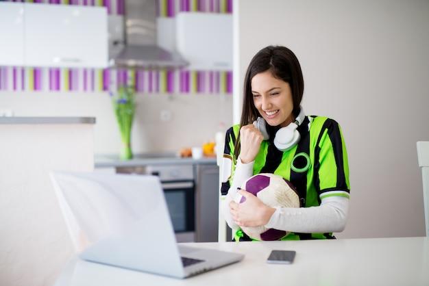 Молодая великолепная взволнованная девочка в зелено-черном свитере наблюдает за футбольным матчем, болеющим за ее ноутбук и держащим шар