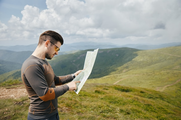 Young gorgeous man using paper map in mountains