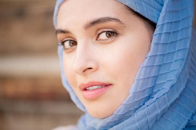 屋外でポーズをしながらまっすぐ見て青いヒジャーブの若い豪華なイスラム教徒の女性