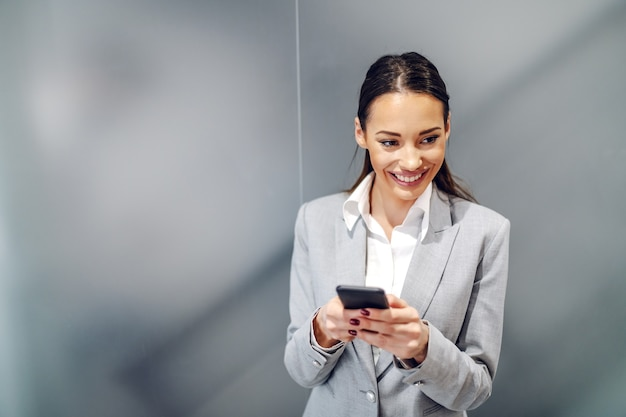 Young gorgeous smiling caucasian businesswoman in suit standing inside corporate firm and using smart phone for texting message to her business partner.