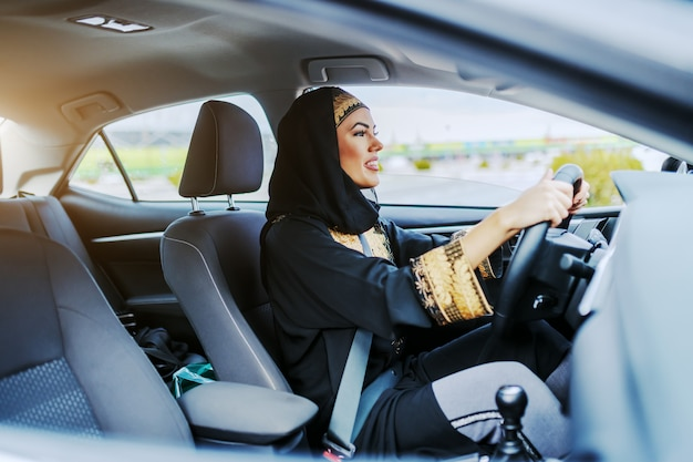 Молодая великолепная улыбающаяся мусульманская женщина в традиционной одежде за рулем своего дорогого автомобиля.