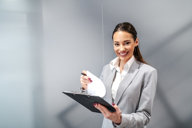 Young gorgeous smiling positive caucasian businesswoman standing inside corporate firm and signing contracts.