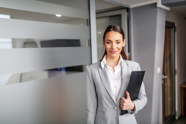 Young gorgeous smiling successful caucasian businesswoman posing in hall of corporate firm and holding clipboard in hands.