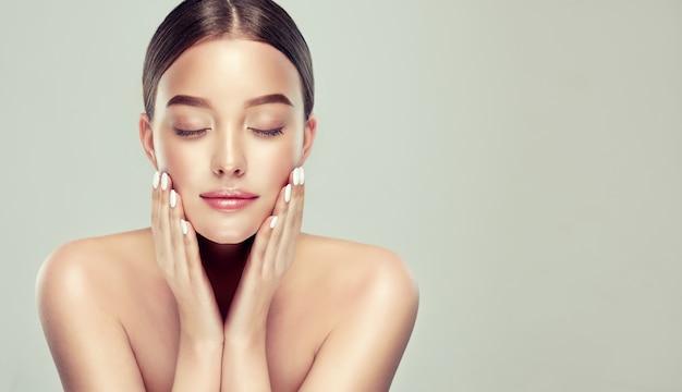Молодая великолепная женщина с чистой свежей кожей и обнаженными плечами увлажняет лицо красивым концептом
