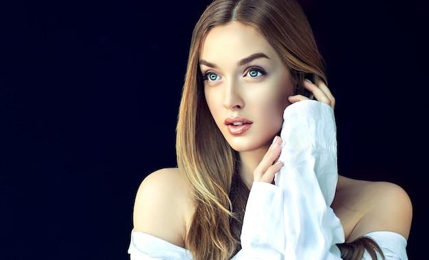 Молодая, великолепная женщина с длинными прямыми волосами и элегантным макияжем трогает собственное лицо