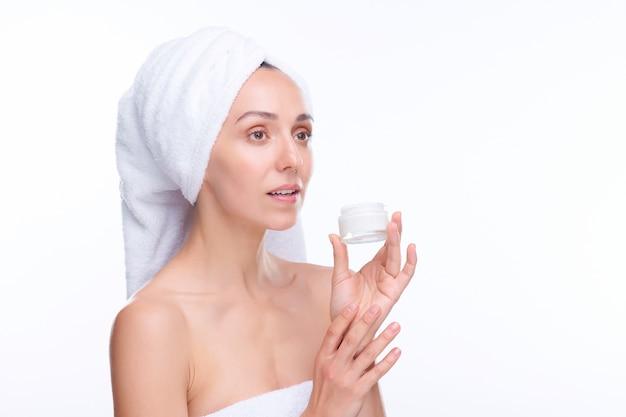 머리에 부드러운 수건을 가진 젊은 화려한 여자가 목욕이나 샤워 후 그녀의 얼굴과 목에 보습 크림을 바를 것입니다