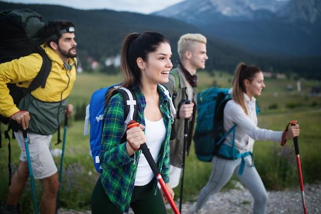 バックパックとクライミングスティックを持って、丘を登る友人の若いグループ