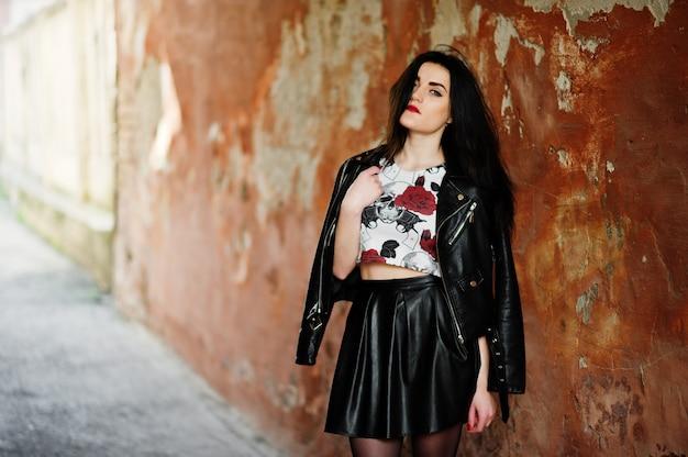 黒革のスカートとグランジの壁にジャケットの若いゴス少女。