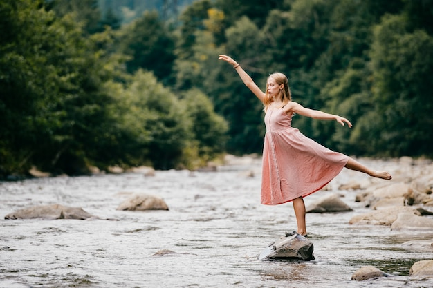 Молодая грациозная балерина девушка балансирует на камне в реке