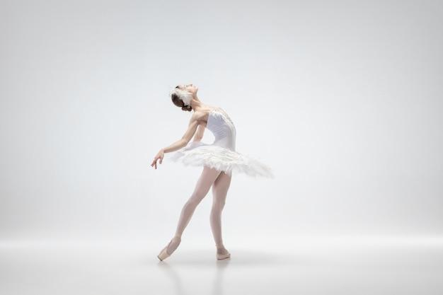 白いスタジオの背景に若い優雅なバレリーナ
